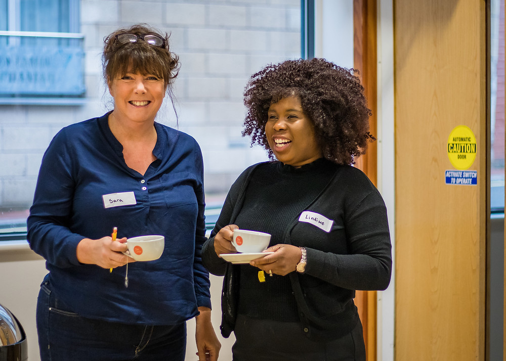 Two women enjoying a cup of tea at the Labour Women's Development Programme