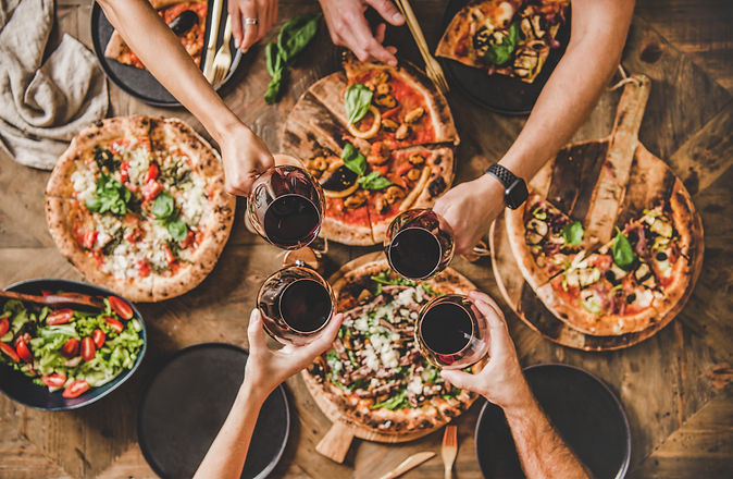 Family or friends having pizza party dinner. Flat-lay of people clinking glasses with red