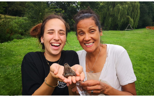 Two smiling women holding a piece of archeological pottery at a dig site