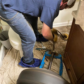 Sewer line being snaked from pulled toilet in Reston, Va