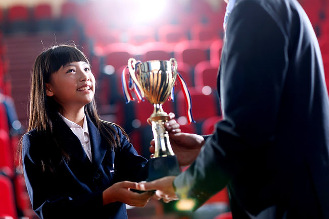 A kid holding a trophey for his academic achievements.