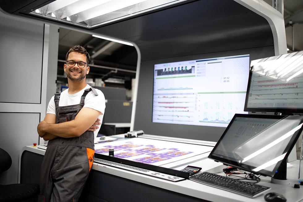 portrait-experienced-print-worker-standing-by-control-desk-modern-printing-house.jpg