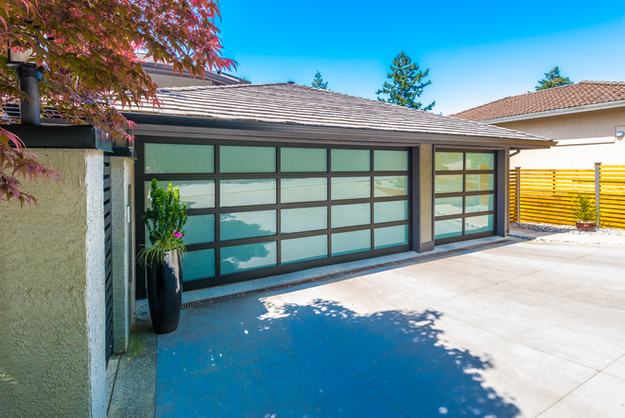 Garage with wide, long nicely paved driv