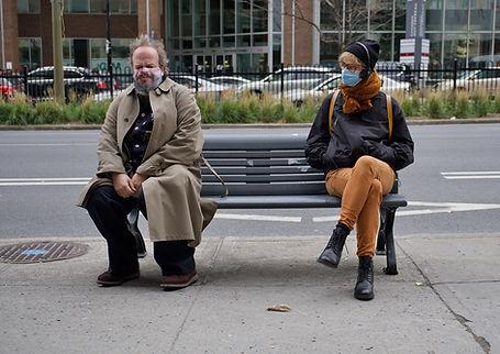 Un personnage assis sur un banc et une spectatrice qui le regarde