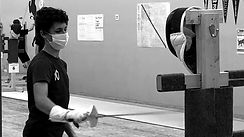 Youth athlete fencer practicing on a target dummy