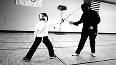 Kid taking a fencing lesson