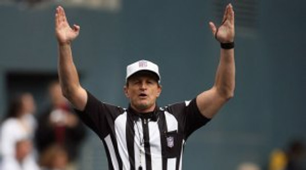 Football referee giving touchdown signal
