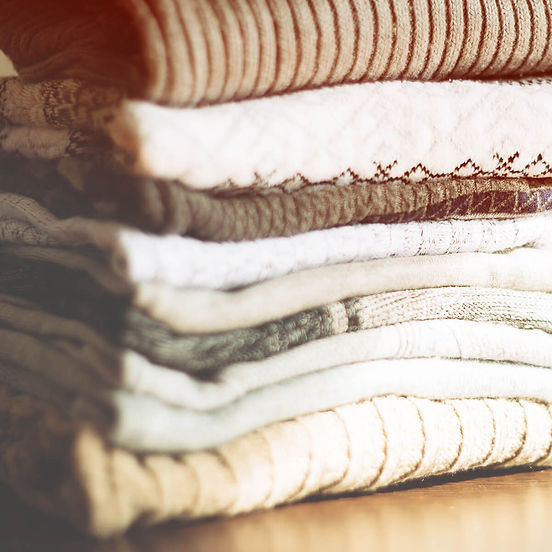A stack of clean, folded and sanitized laundry delivered by Lavado Laundry Delivery Service