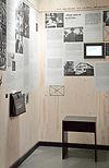 Eine Plakatwand mit aufgeklebten Texten über die Flucht der Familie Mann und ein literariches Quiz auf einem Monitor.