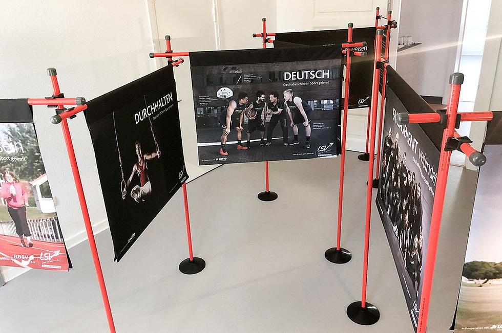 Schwarz-weiß bedruckte Banner, die an roten Sportstangen hängen.