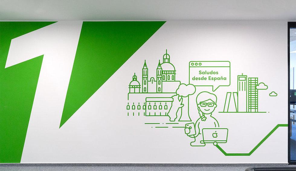 Eine Wand mit einer grünen Ecke, mit einer großen weißen Eins. Eine Frau als grüne Strichgrafik mit einem Laptop und eine Handy. Im Hintergrund Wolkenkratzer.