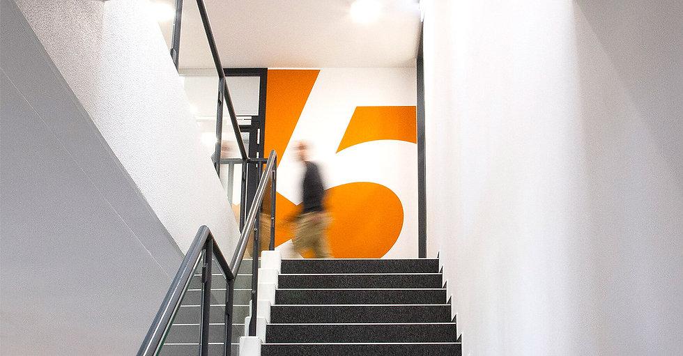 Eine orange Wand mit einer großen weißen Fünf. Im Vordgerund einer lange Treppe mit grauem Teppich. Es ist ein Mann schemenhaft zu erkennen.