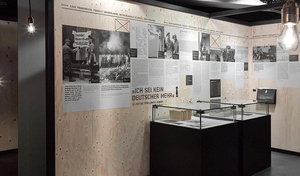 Eine Plaktwand in der Sonderausstellung Fremde Heimat, die mit Texten beklebt sind und von der Flucht der Familie Mann vor dem Krieg erzählen.