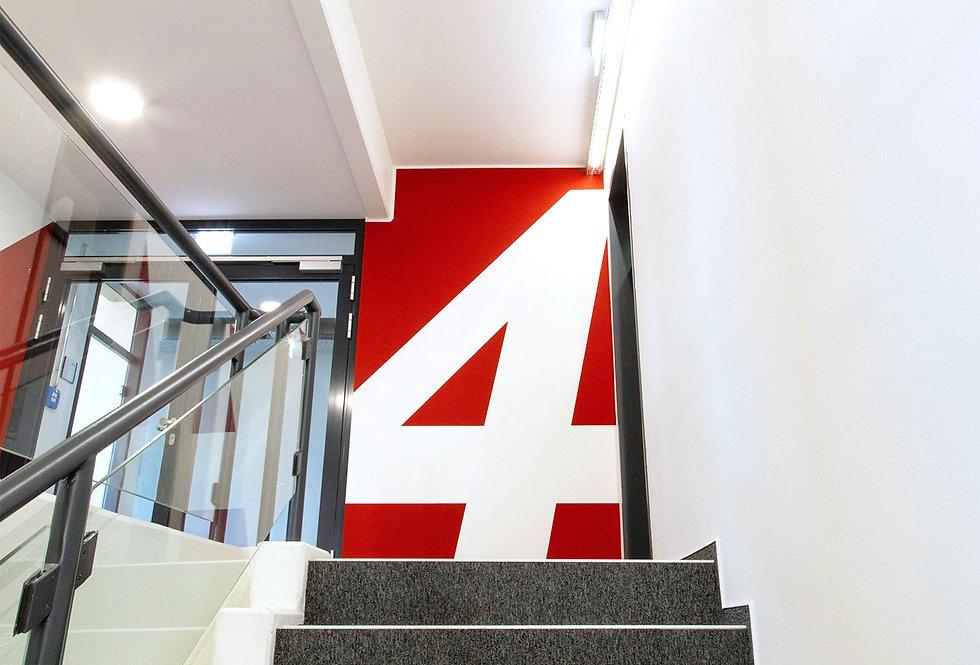 Eine große weiße Zahl auf einer roten Wand am Ende einer Treppe, die man hinauf geht.