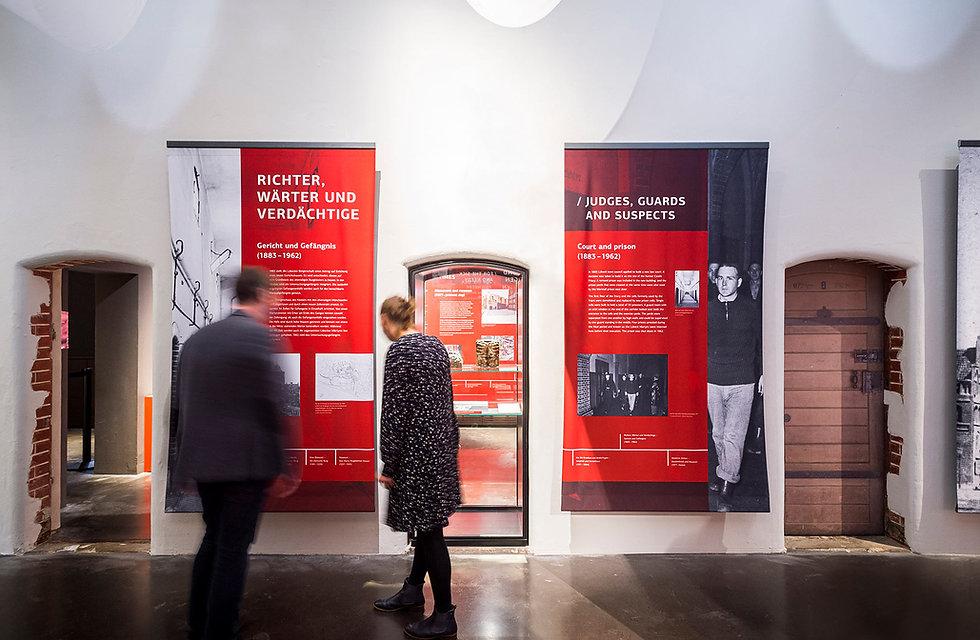 Zwei Menschen vor bedruckten Bannen in eie Ausstellung