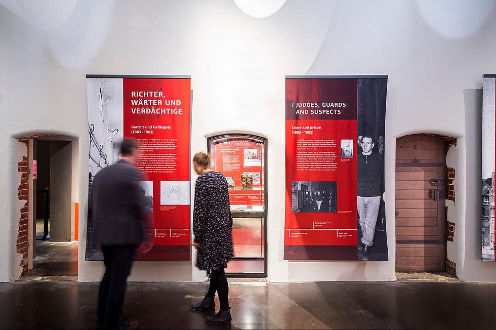 Zwei Menschen vor bedruckten Bannern in einer Ausstellung