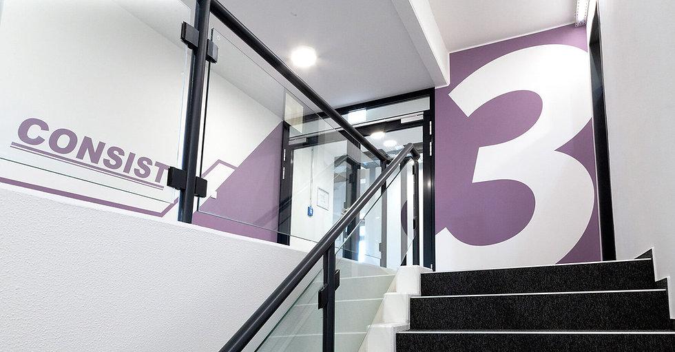 Eine Wand in lila mit einer großen weißen Drei. Im Vordergrund ein Treppenaufgang mit grauem Teppich. Im Hintergrund das Logo der Softwarefirma Consist.