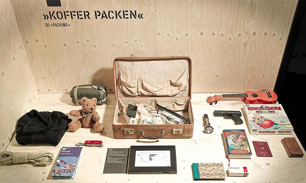 Ein Koffer auf einem Tisch. Rundherum Dinge, die Kinder mit auf eine Flucht nehmen würden.