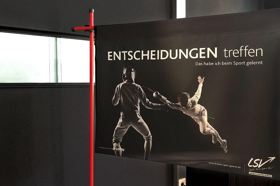 Ein schwarzes Banner mit zwei Sportlern, die fechte und der Aufschrift Entscheidungen treffn. Das habe ich beim Sport gelernt. Unten recht in der Ecke das Logo des Landessportverbandes Schleswig-Holstei