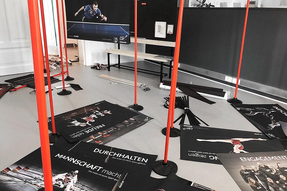 Bedruckte Banner einer Ausstellung liegen auf dem Boden verteilt. Im Vordergrund sieht man rote Stangen.