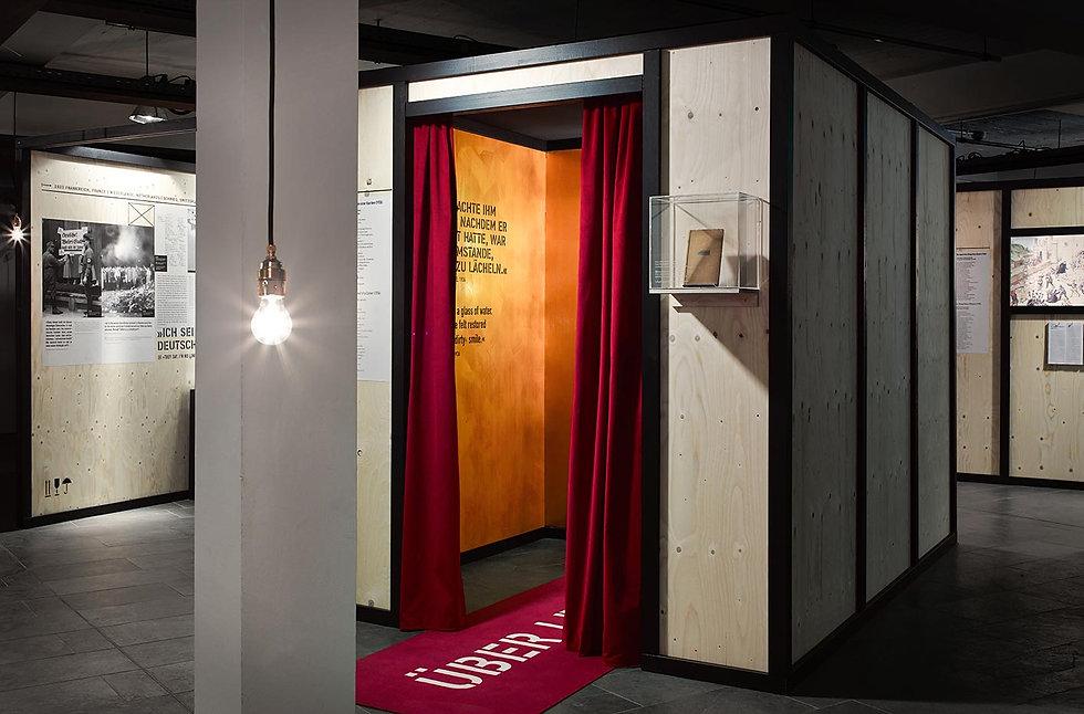 Eine begehbare Holzbox mit roten Vorhängen, die das Thema Mephisto von Klaus Mann verhandelt.