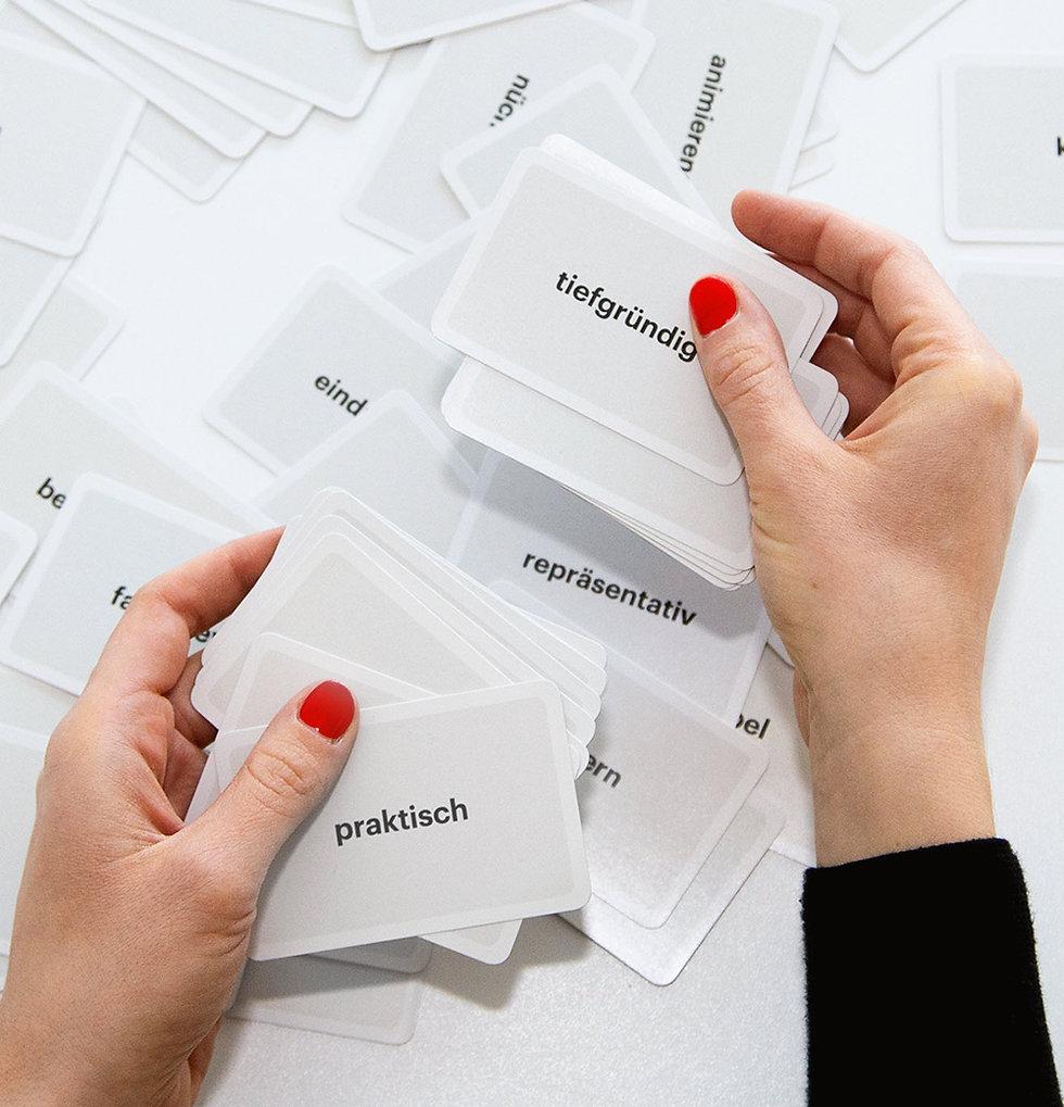 Zwei Hände mit rotlackierten Fingernägeln, die über einem Tisch mit vielen Spielkarten liegen.