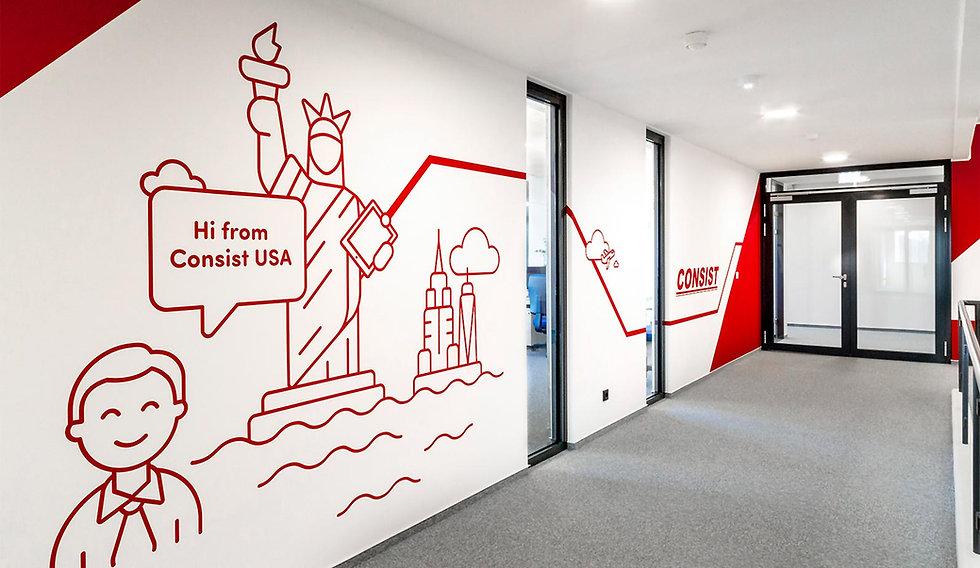 Eine rote Strichgrafik von der Freiheitstatue an der Wand auf einem Flur mit grauem Teppich.