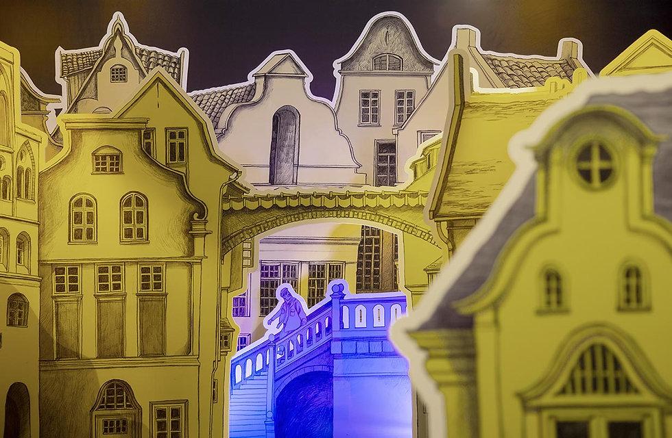 Ein geschichtetes Papiertheater. Professor Unrat läuft mit wehendem Schal durch die engen Gassen Lübecks.