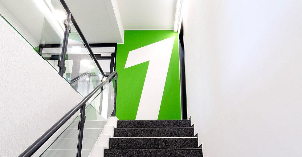 Eine grüne Wand mit einer großen weißen Eins. Im Vordergrund Stufen, die nach oben führen, mit grauem Teppich