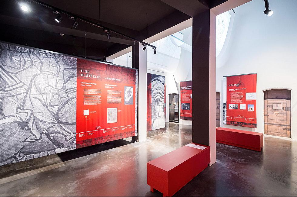 Blick in eine Ausstellung mit rotbedruckte Banner und Ausstellungsmöbeln.