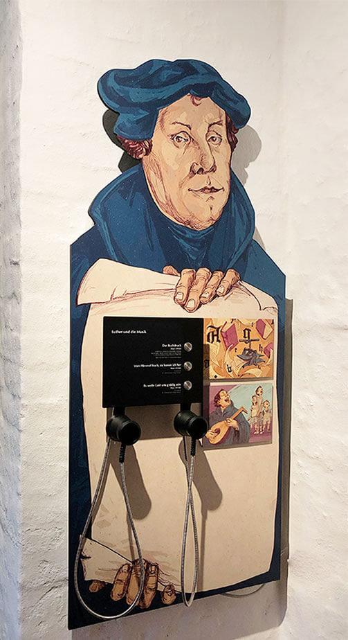 Ein Wandtableau mit einer Illustration von Martin Luther und einer Hörstation mit Kirchenlieder.