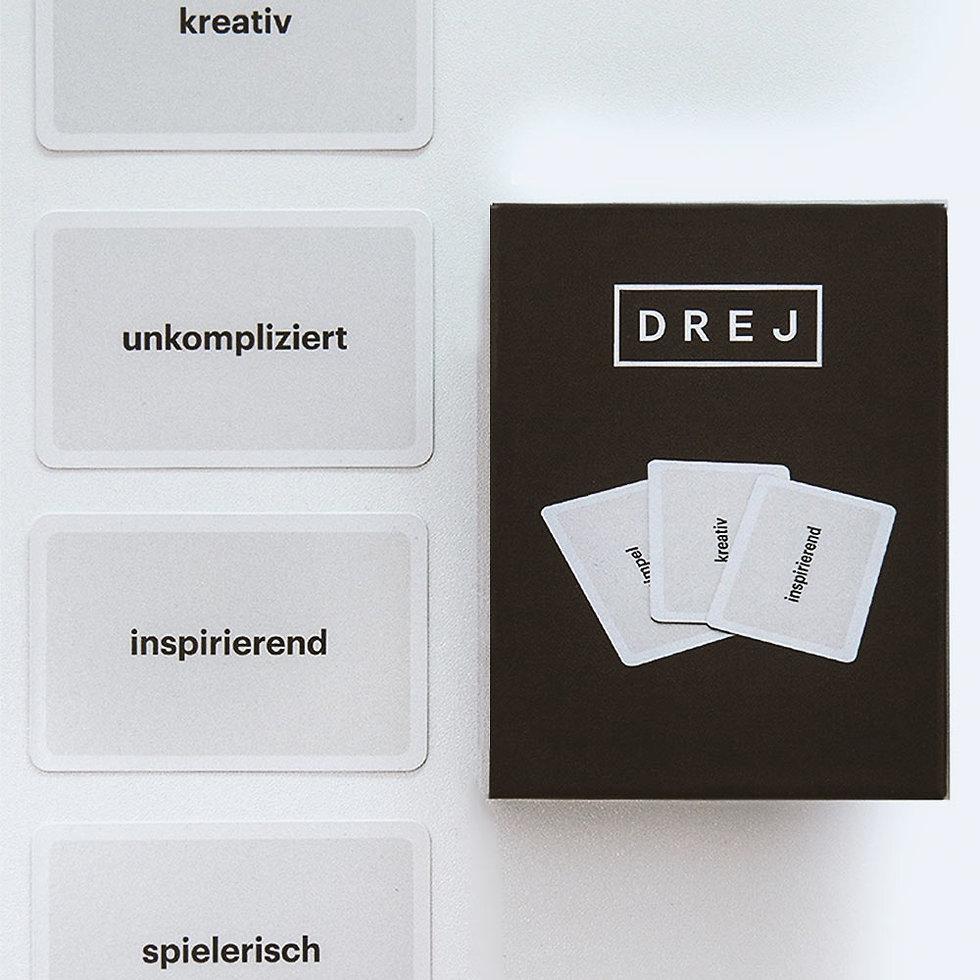 Vier Spielkarten mit unterschiedlichen Adjktiven, daneben eine schwarze Spielkartnbox mit dem Logo der Firma drej.