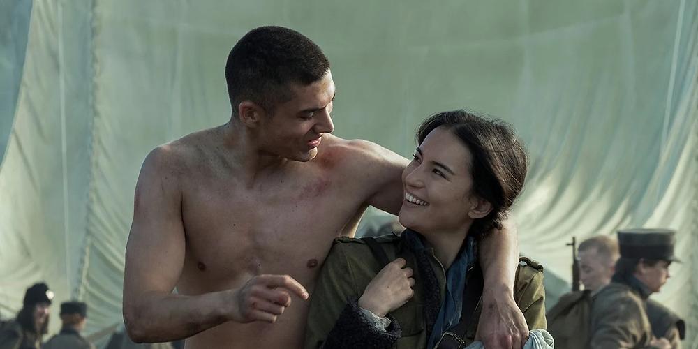 Fotograma de la serie Sombra y hueso. Mal, descamisado tras un combate, bromea con Alina. Le pasa el brazo por los hombros (él es más alto) y ambos se miran, riendo.