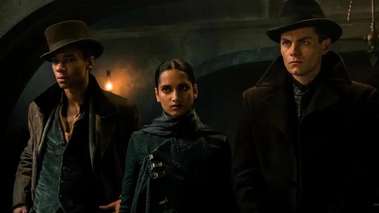 Fotograma de Sombra y hueso. Plano medio de Jesper, Inej y Kaz, los tres miembros de los Despojos. Visten ropa oscura y tanto Jesper como Kaz llevan sombreros de ala y abrigos pesados.