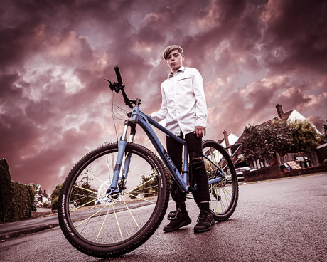Boy on Bike and thunder storm by Adam Soller Photography