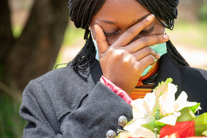 a young black woman mourning, wearing bl