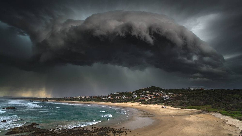 A thick storm cloud over Lighthouse Beach shows rain falling over Port Macquarie and Bonny Hills in 2017. Photo: Ivan Sajko (Ocean Drive Images)