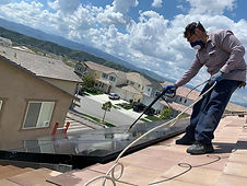 A Speedy's Pes Solutions Service Technician cleaning removing pigoen droppings off a solar panel