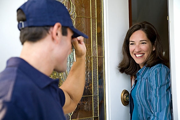 Image of a Speedy's service technician greeting a customer st her door