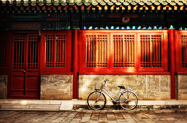 One bicycle in front of oriental red building in urban Asia city on street sidewalk on sun