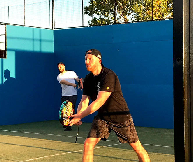 Two men in action during a padel tennis match in Calgary, Alberta
