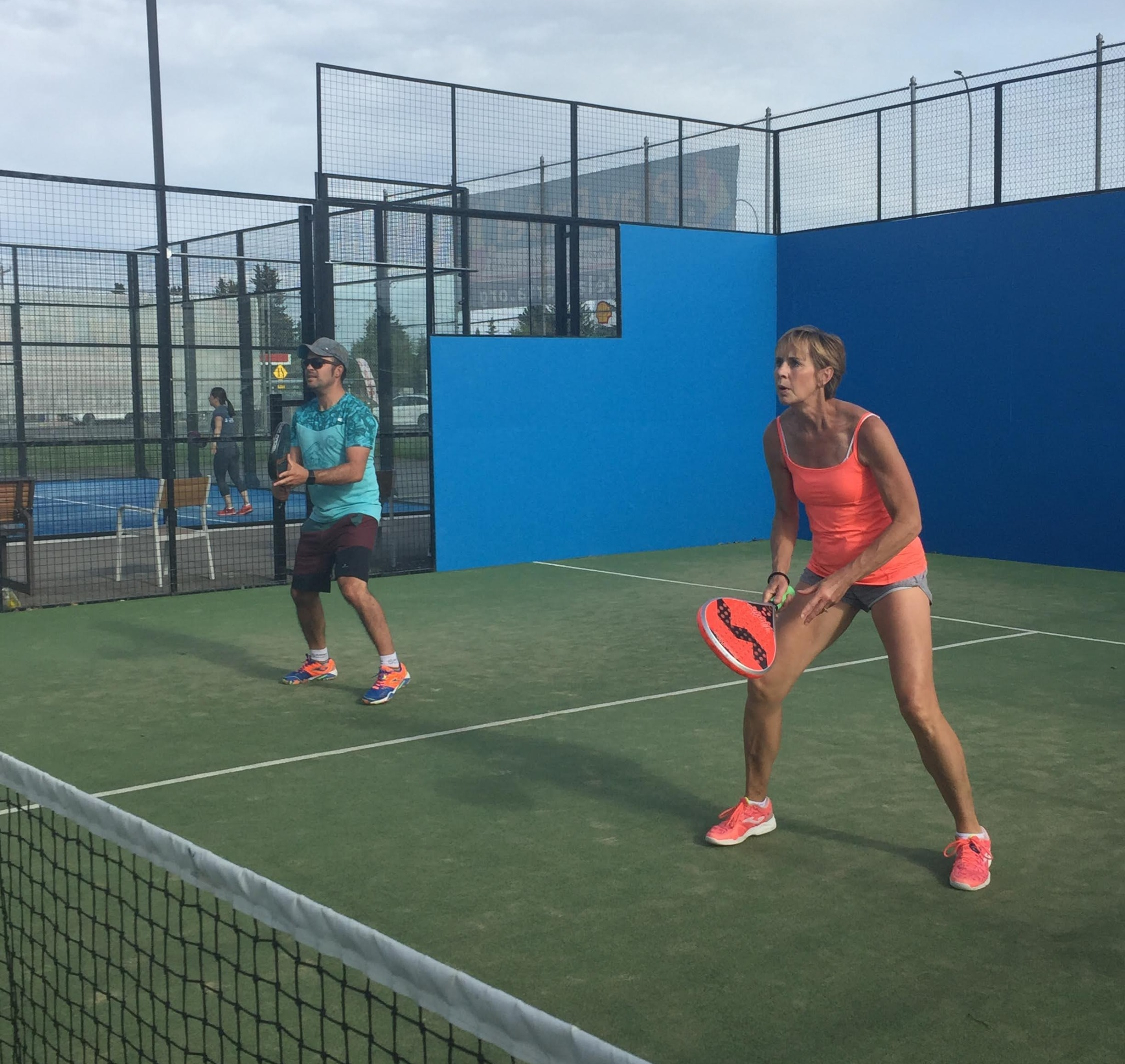 Man and Woman playing doubles Padel Tennis