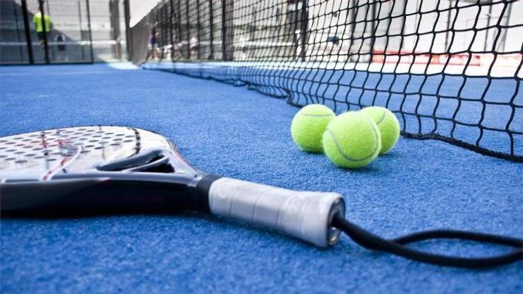A padel tennis racquet lies on an outdoor blue turf court next to a tennis ball
