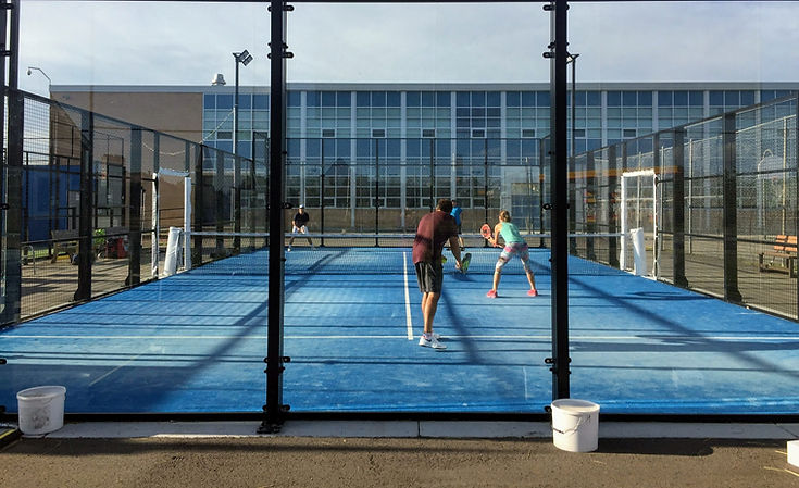 Doubles match of padel tennis being played on an outdoor court in Calgary, Alberta