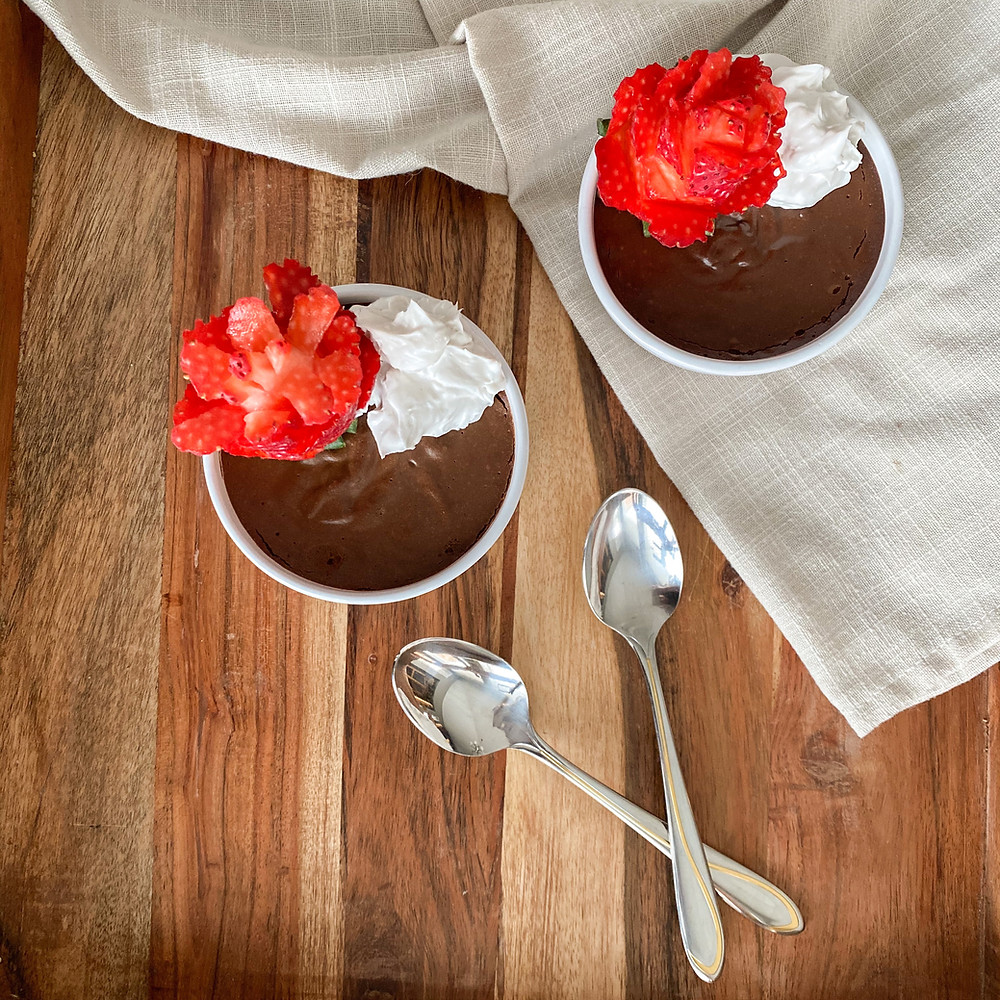 chocolate mousse on a wooden board with two spoons, whip cream, and strawberries shapes like roses.