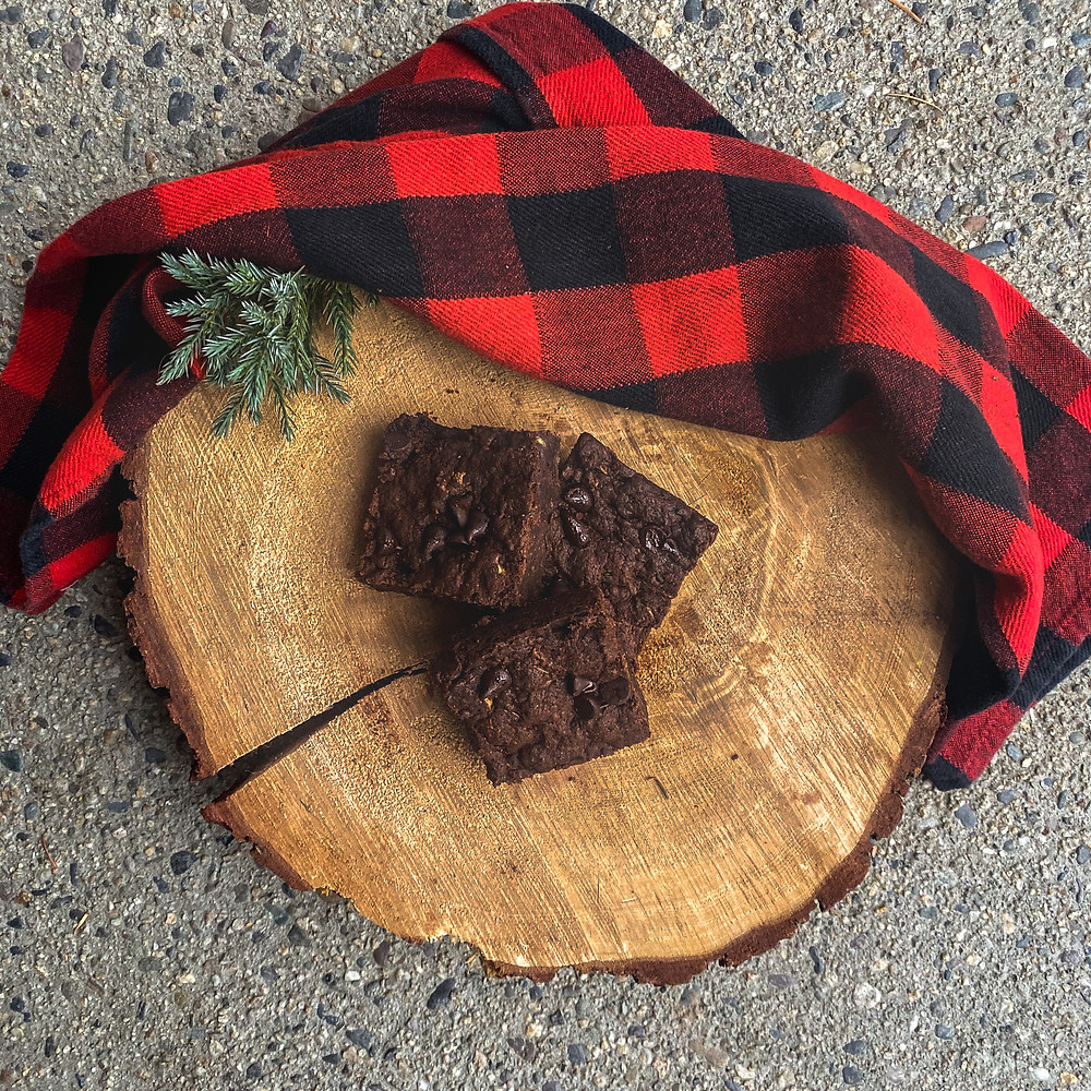 vegan and gluten-free chocolate zucchini brownies on a wooden tree stump with a red and black plaid blanket looking delicious.