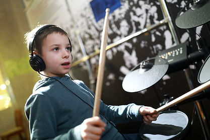 Serious boy with headphones playing drum