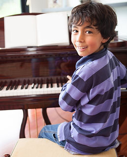 Happy boy playing the piano at home.jpg