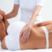 Therapist doing lower back massage on wo