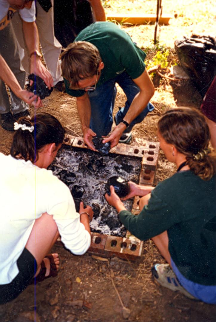 Workshop participants remove low-fire black pots from the kiln